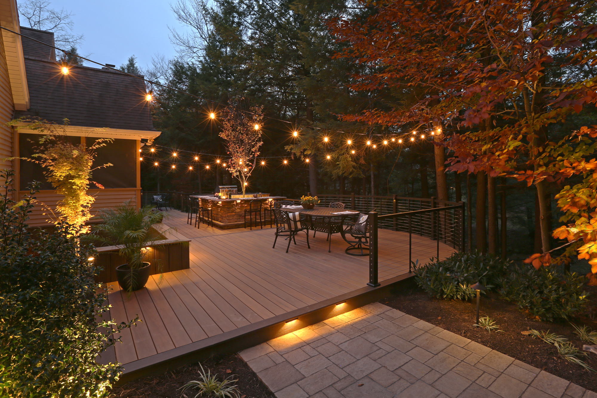 This custom deck comes to life when the sun goes down and the landscape lighting turns on. The space is stunningly finished with Edison string lights creating a romantic environment.