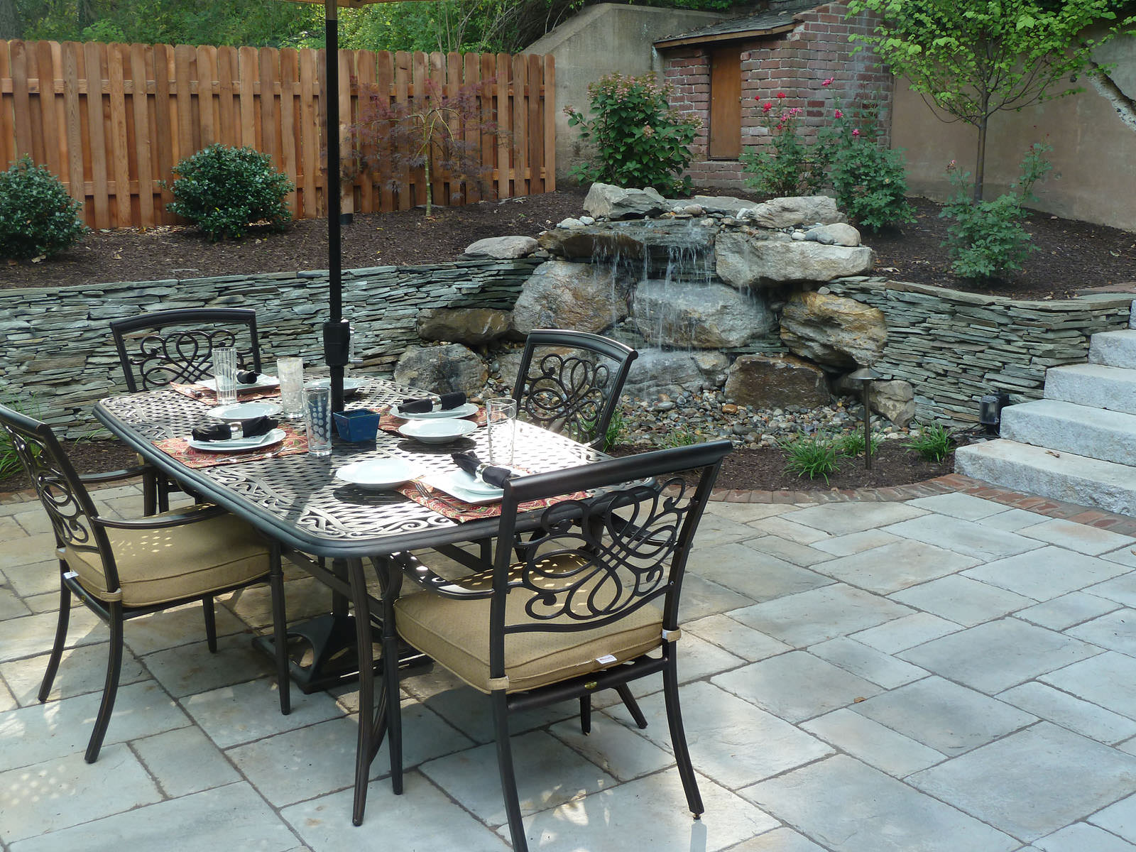 This al fresco dining area is beautifully complimented by the soothing sound from the adjacent trickling water feature that seamlessly blends right into the hillside.