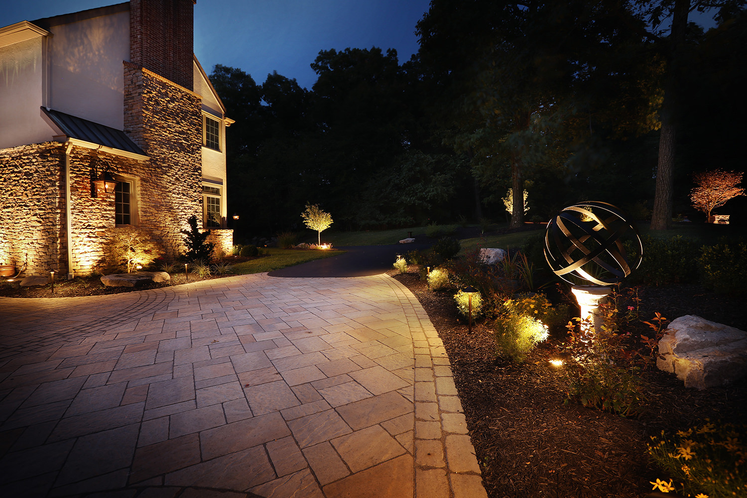 Soft and warm LED landscape lighting beautifully highlights the home and surrounding landscape features once the sun sets for the evening.