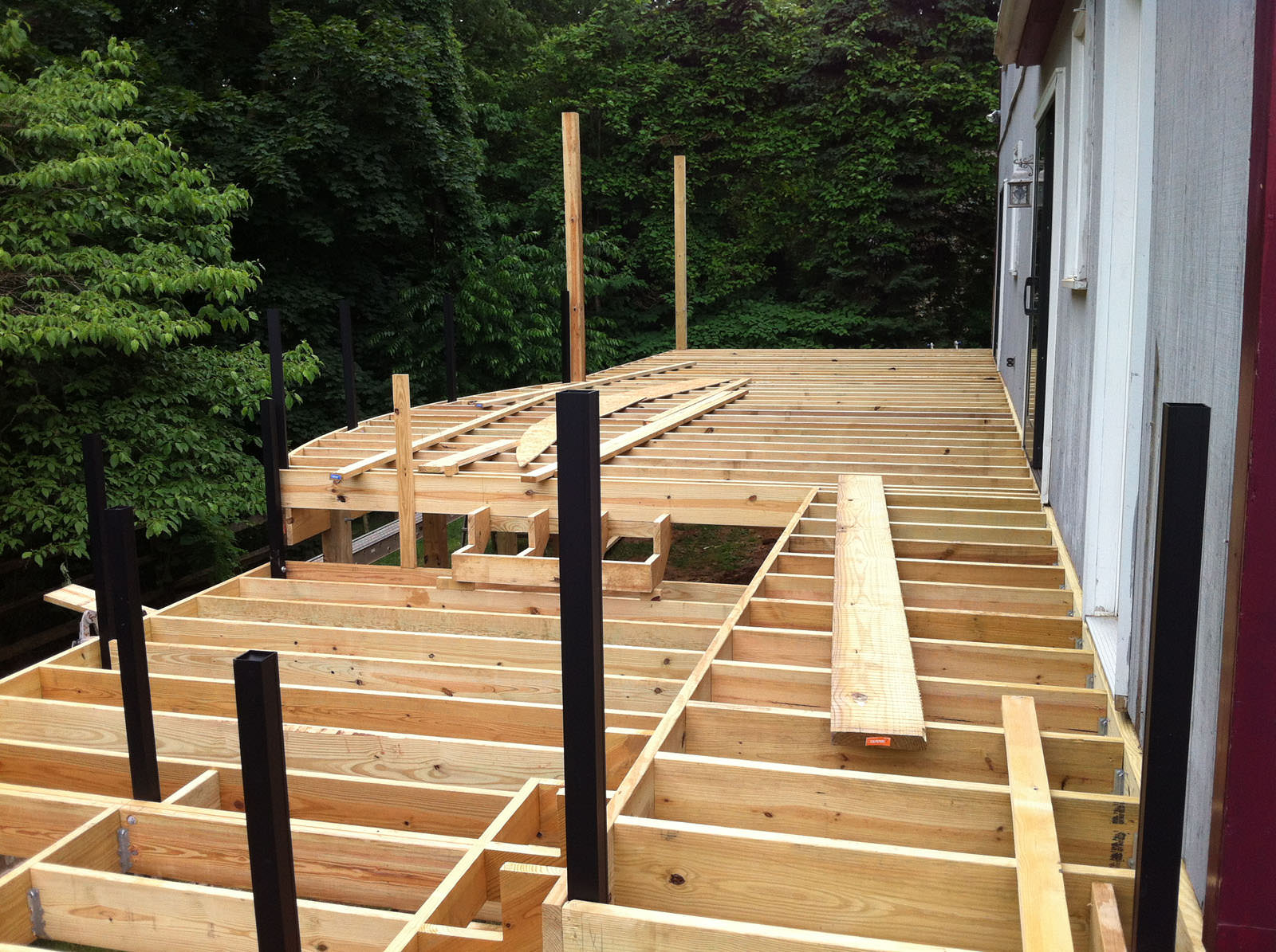 With the old pressure treated deck removed, the new deck framing started right away!