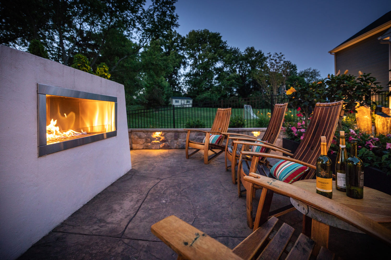 When the sun sets low, this outdoor living space comes alive!  Low voltage accent lighting beautifully highlights the features and colorful plantings around the patio while the fireplace adds warmth and a romantic ambiance to the environment.