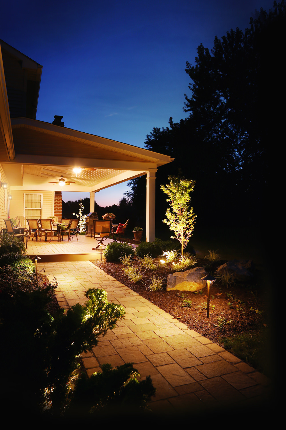 The new paver walkway, along with perennial landscaping and warm LED landscape lighting creates the perfect soft and welcoming complement to the space.