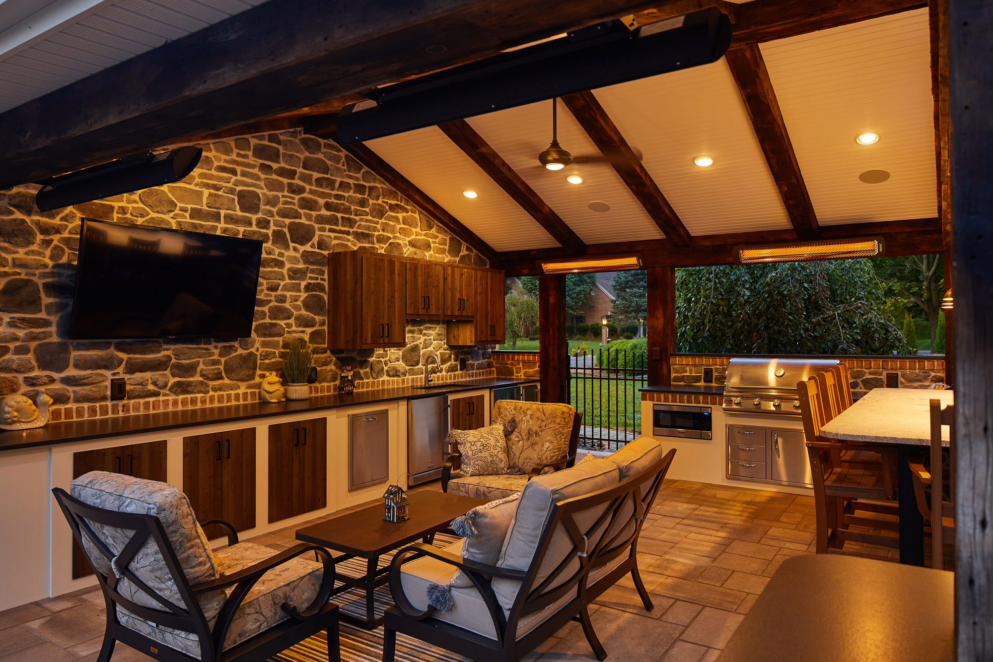 This outdoor living space beautifully combines rustic and contemporary, all while providing ample room for a complete kitchen, storage, dining and lounging!